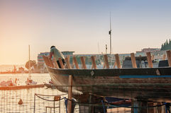 Workshop for restoration of ships on the shores of the Adriatic sea. Man repairs a boat at dawn at sunrise. Royalty Free Stock Photos