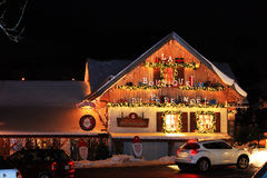 Workshop Santa Claus wooden house. Facade is decorated with lights and pear on a background of the night sky in the windows of warm light christmas new year royalty free stock photography