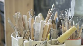 In workshop there are a lot of different tools for handicrafts in cups. To work with clay on the shelf metal devices for working with manufacture of dishes and stock video footage