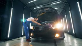 Workshop unit with a male worker fixing a vehicle. 4K stock video footage