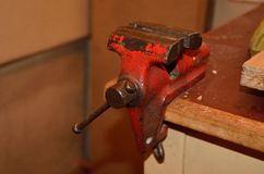 Workshop with vice. Old red vise on the table in the workshop Stock Photo