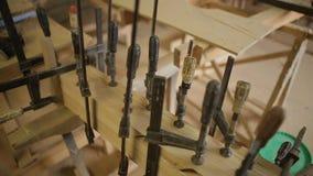 Workshop voor de vervaardiging van houten producten, hulpmiddelen om het werkstuk, klem, materiaal, langzame motie te beveiligen stock videobeelden