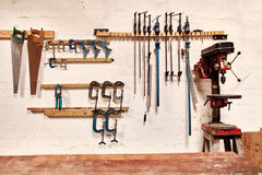 Workshop wall with tools in rows alongside a drill press Stock Image