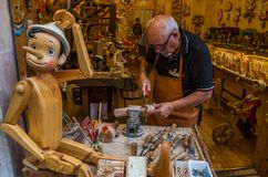ROMA, ITALY - JULY 2017: Workshop where the master scrutinizes the handmade traditional wooden toys of Pinocchio. Workshop where the master scrutinizes the royalty free stock photo