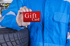 Workshop worker holds a gift card. Closeup of male workshop worker with blue uniform, showing a gift card Stock Photo