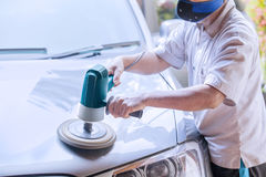 Workshop worker polishing the car. Image of male workshop worker using an auto polisher to polish the car body Stock Photography