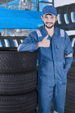 Workshop worker shows OK sign. Arabic workshop worker standing next to a pile of tires while showing thumb up Stock Image