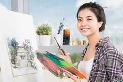 In workshop. Young Asian woman working on painting in a workshop Royalty Free Stock Image