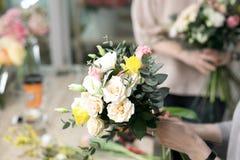 Workshopbloemist, die boeketten en bloemstukken maken Vrouw die een boeket van bloemen verzamelen Zachte nadruk stock fotografie