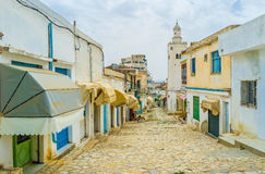 The workshops of El Kef. EL KEF, TUNISIA - SEPTEMBER 5, 2015: The working neighborhood with numerous workshops and stalls with the high white minaret on the Royalty Free Stock Image