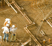 Worksite inspection. Engineers, foremen and regulatory authorities checking blueprints against work done at a crucial phase in a housing project Royalty Free Stock Photography
