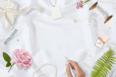 workspace Κάρτες γαμήλιας πρόσκλησης, φάκελοι τεχνών, ρόδινα και κόκκινα τριαντάφυλλα και πράσινα φύλλα στο άσπρο υπόβαθρο σατέν στοκ εικόνες με δικαίωμα ελεύθερης χρήσης