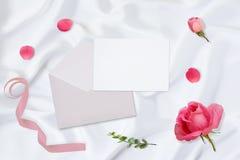 workspace Κάρτες γαμήλιας πρόσκλησης, φάκελοι τεχνών, ρόδινα και κόκκινα τριαντάφυλλα και πράσινα φύλλα στο άσπρο υπόβαθρο σατέν στοκ εικόνα