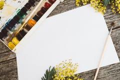 workspace Πλαίσιο στεφανιών με τα mimosas, τα watercolors, το πινέλο και την εκλεκτής ποιότητας κάρτα στο ξύλινο υπόβαθρο Στοκ Φωτογραφίες