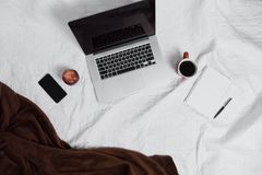 Workspace on bed. Working space on bed with coffee and laptop. Morning flat lay Royalty Free Stock Image