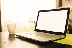 Workspace with blank screen laptop on the table at home. Workspace with blank screen laptop on the table in room at home Royalty Free Stock Image