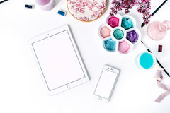 Workspace. Brushes, palette, bouquet of lilac, tablet and smartphone  on white background Stock Photo
