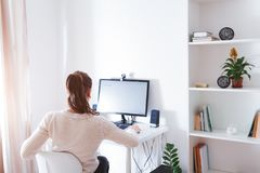 Workspace of business woman. Woman works on computer in light sunny room . Modern design with white furniture. And new technologies Stock Image