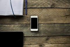 workspace Caderno, lápis e telefone na mesa de madeira velha Imagens de Stock