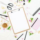 Workspace with clipboard, notebook, flowers and accessories on white background. Blog concept. Flat lay, top view. Workspace with clipboard, notebook, flowers royalty free stock photos