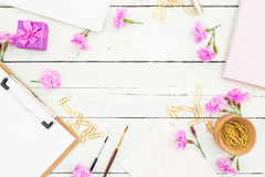 Workspace with clipboard, notebook, pink flowers and accessories on  rustic table. Beauty blog workspace. Flat lay, top view. Royalty Free Stock Images