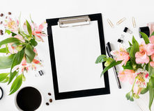 Workspace with clipboard, office accessories, coffee and bouquet. Workspace with clipboard, office accessories, cup of coffee and bouquet of flowers. Flat lay Royalty Free Stock Image