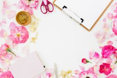 Workspace with clipboard, pastel roses and accessories on white background. Flat lay, top view. Copy space. Workspace with clipboard, pastel roses and stock images