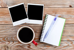 Workspace with coffee cup, instant photos, note paper and notebo Royalty Free Stock Photography