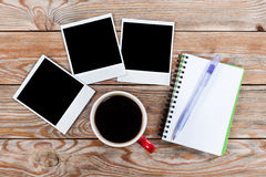 Workspace with coffee cup, instant photos, note paper and notebo Stock Photos
