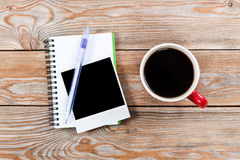 Workspace with coffee cup, instant photos, note paper and notebo Stock Photo