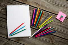 Workspace with colored pencils and notebook on old Royalty Free Stock Images