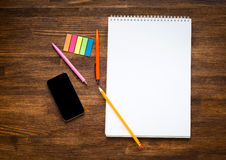Workspace with colored pencils and notebook on old Stock Images