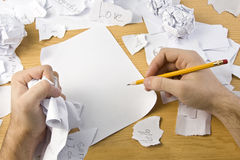 Workspace with crushed paper and hands Royalty Free Stock Photography