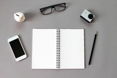 Workspace desk with blank notebook, pencil, eye glasses, small action camera, piggy bank and smart phone on gray background Royalty Free Stock Image