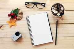 Workspace desk with notebook, pencil, pine cones in tea wooden cup, eye glasses, christmas decoration and small action camera on w Stock Images