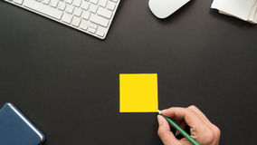 Workspace desk with post it and hand. Copy space background  black Stock Images