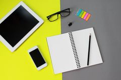 Workspace desk with tablet computer, blank notebook, pencil, eye glasses, smart phone, clip and paper note on yellow and gray back Stock Image