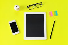 Workspace desk with tablet computer, pencil, eye glasses, sticky paper note, piggy bank and smart phone on yellow background Stock Photos