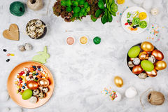 Workspace with easter decoration. Painted eggs in trays, candy, flowers with copy space. Holiday background. Flat lay, top view stock photography