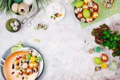 Workspace with easter decoration. Painted eggs in trays, candy, flowers with copy space. Holiday background. Flat lay, top view Stock Image