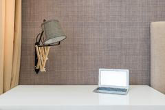 Workspace. Empty table with walllight and notebook Stock Photography