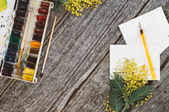 workspace Envolva o quadro com mimosas, aquarelas, tinta da pena e cartão do vintage no fundo de madeira moke acima imagens de stock royalty free