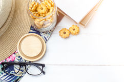 Workspace with eyeglasses, book, snacks and sun hat on wooden ba Stock Photography