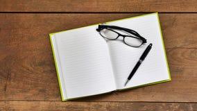 Workspace för bästa sikt med den tomma anteckningsboken, exponeringsglas och pennan på woode Royaltyfri Fotografi