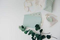 workspace Folhas do cartão e do eucalipto do convite do casamento no fundo branco foto de stock