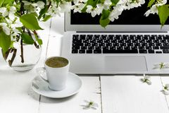 Workspace with girl`s hand on laptop keyboard and cup of coffee, white spring apple tree flowers on white woodden background. Vie royalty free stock photography