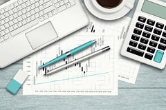 Workspace with graph, computer, graph, calculator and stationery. Over blue desk Stock Images