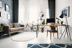Workspace hairpin desk with mockup computer, lamp and decor stan. Ding in living room interior with posters on the wall, round carpet, sofa with pillows and bike royalty free stock photo