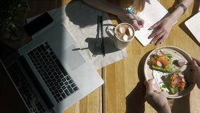 Workspace with Hand touch keyboard on laptop computer, notebook, sandwiches in cafe morning. Top view. Freelancer stock video footage