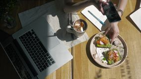 Workspace with Hand touch keyboard on laptop computer, notebook, sandwiches in cafe morning. Top view. Freelancer stock footage